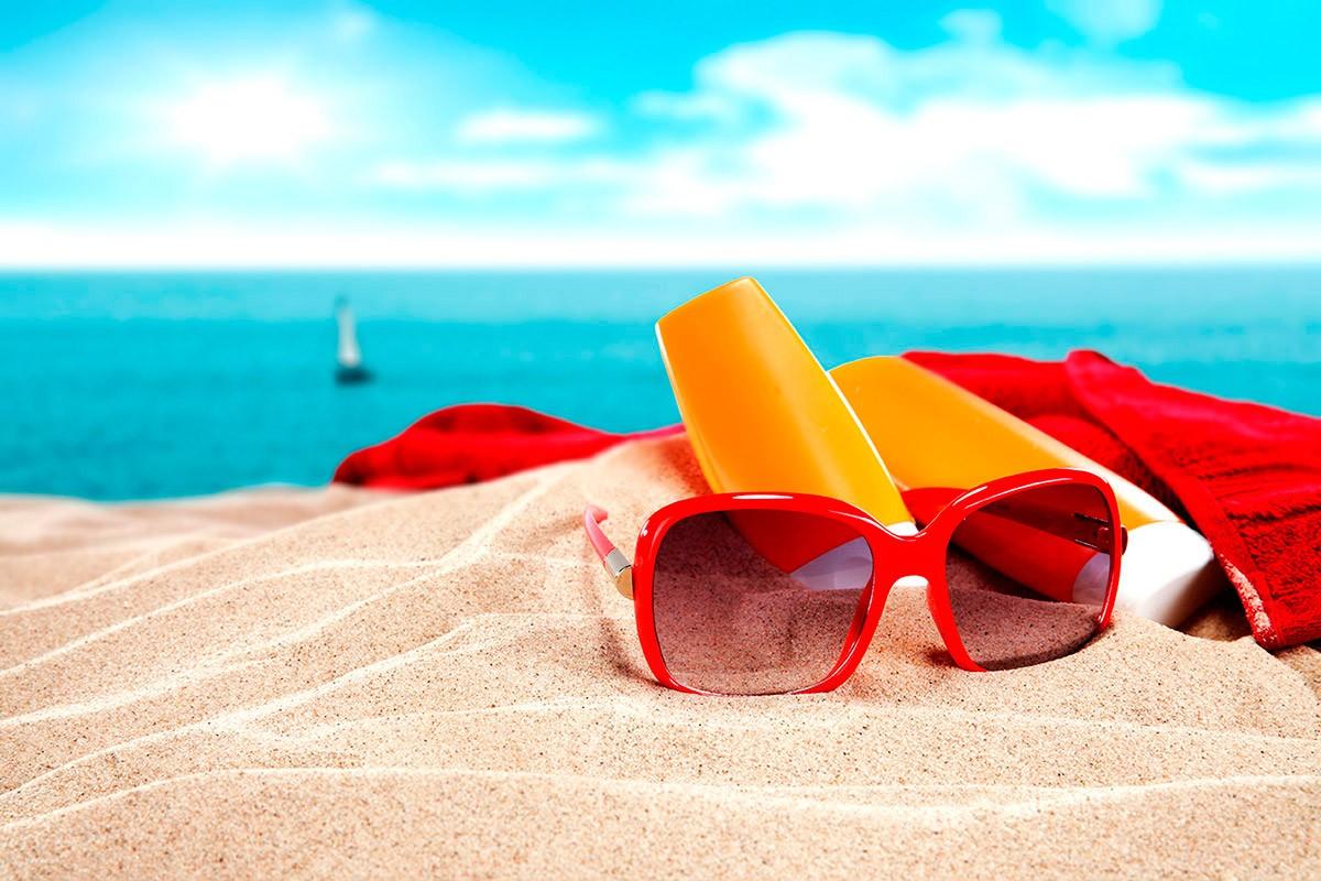 Lunette de soleil, crème solaire et serviette de bain sur la plage