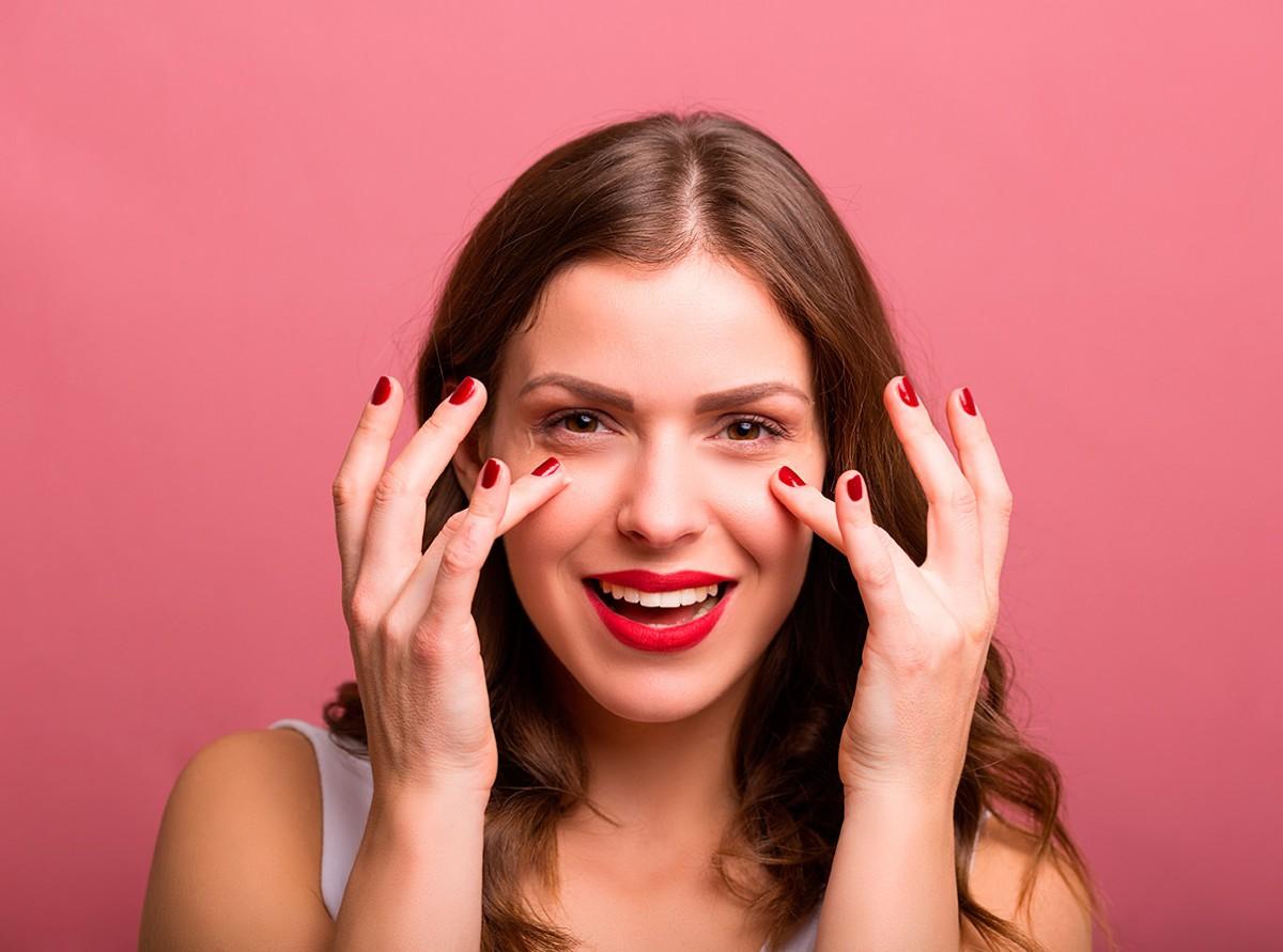 Femme sourriante mettant de la crème sur son visage