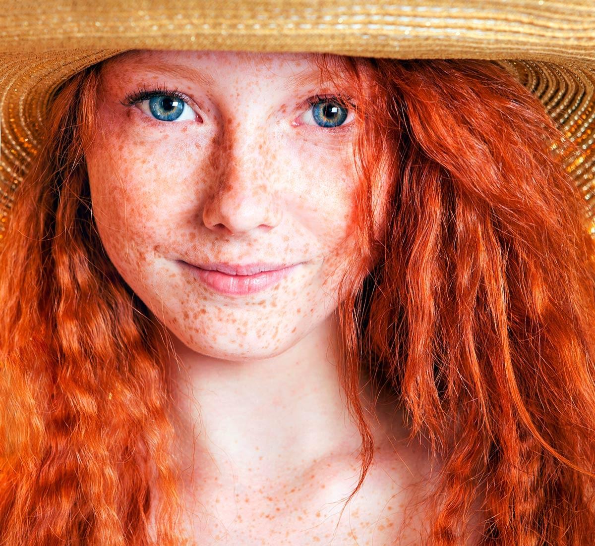 Femme rousse avec un chapeau de paille