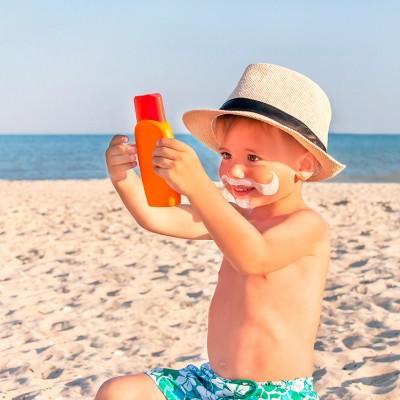Enfant avec un chapeau tenant de la crème solaire sur la plage
