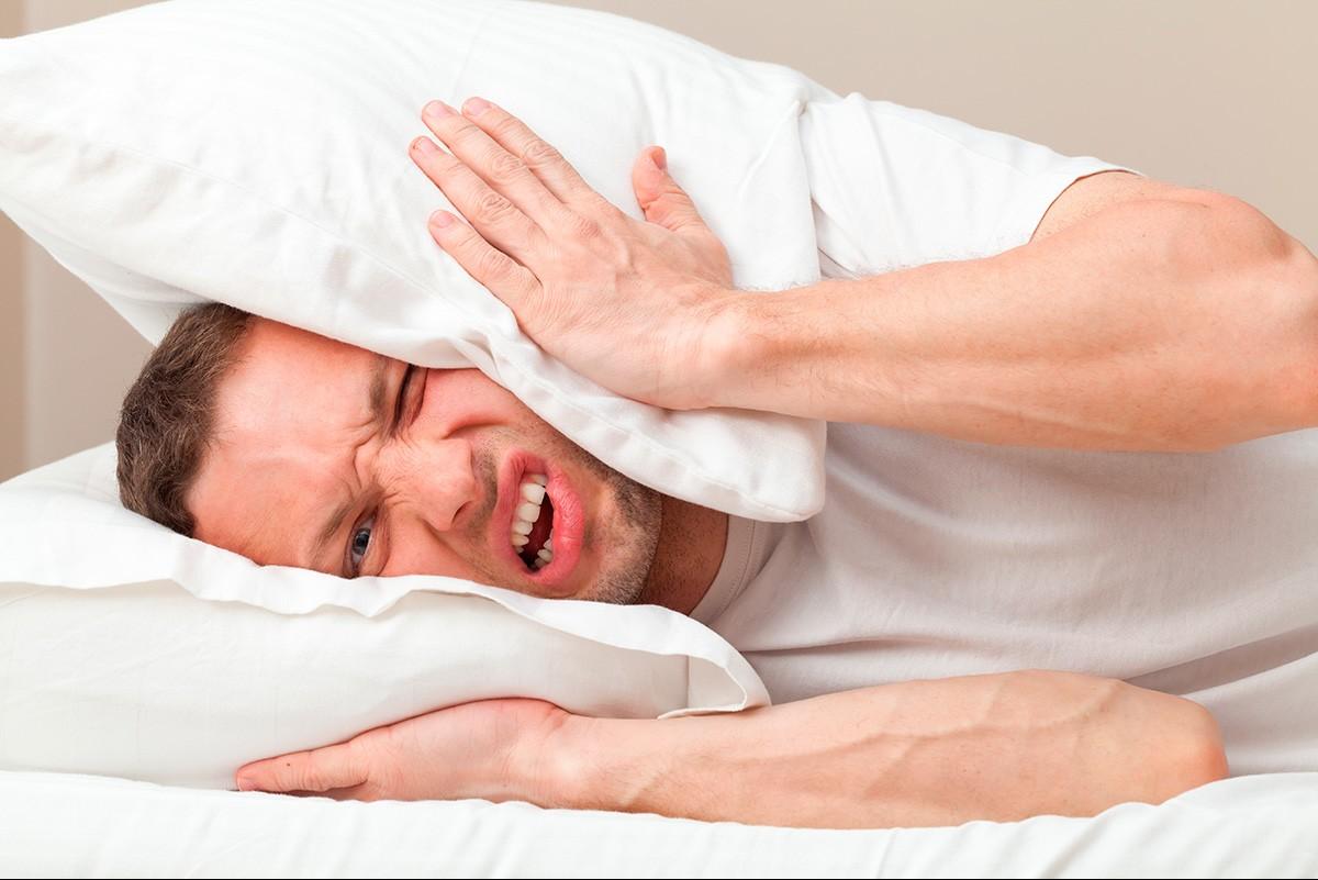 Homme allongé dans un lit se bouchant les oreilles avec un oreiller