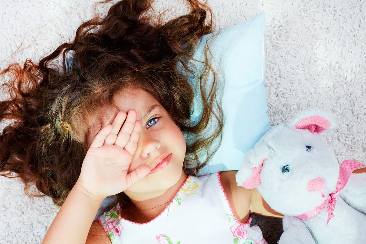 Petite filles dans un lit avec un doudou