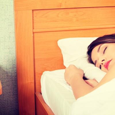 Femme qui dort avec un réveil à sa gauche