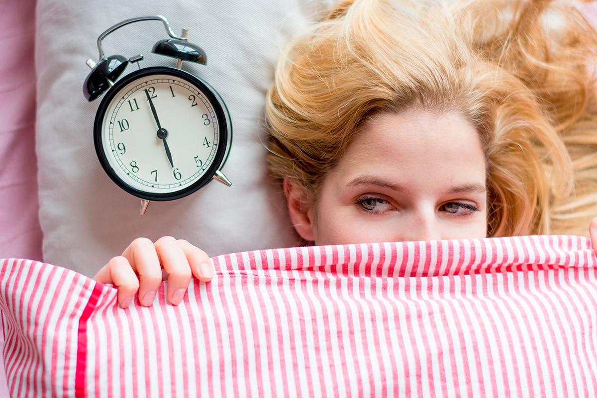 Femme blonde sous une couette avec un réveil sur la gauche de son oreiller